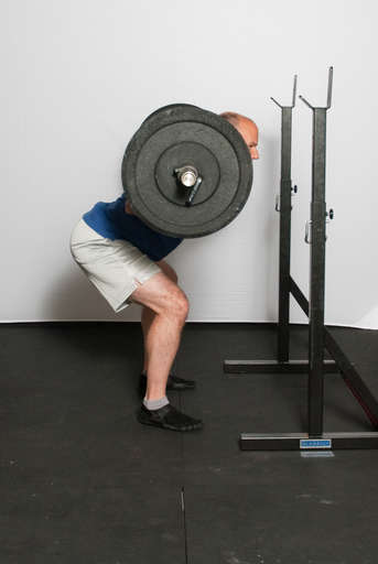 Extend your legs and push the weight up. Remember to keep your weight on your heels and your back arched.