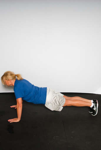 Push yourself up to a plank position by straightening your arms. Continue to keep butt down and aligned with back throughout movement.
