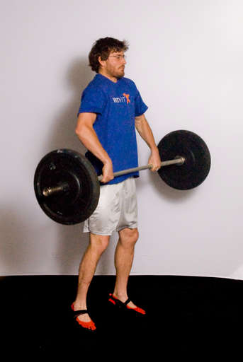 As the barbell reaches mid-thigh, jump upward by extending your hips, legs and ankles. Most of the power for the lift should come from your hips and legs, not from your arms.