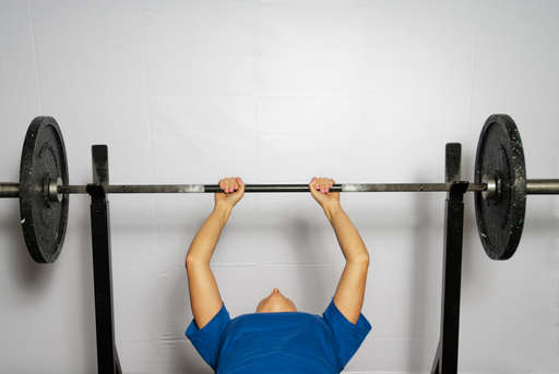 Lie flat on your back on a bench with your feet flat on the floor. Grip the barbell directly above your shoulders so that your knuckles are facing you. Your hands should be closer together than for a normal [bench press].