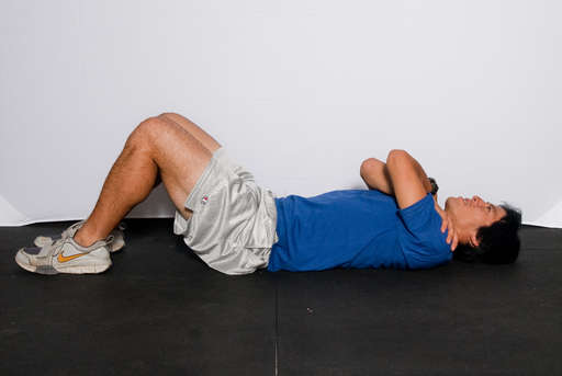 Lie flat on your back with your knees bent and feet flat on the floor. Cross your arms across your chest.