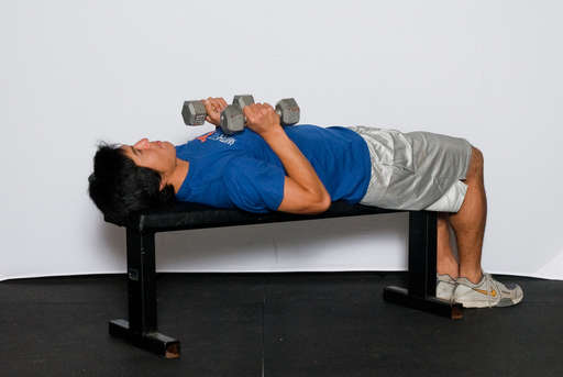 Lie face up on a weight bench with your feet flat on the floor. Hold the dumbbells in an overhand grip.