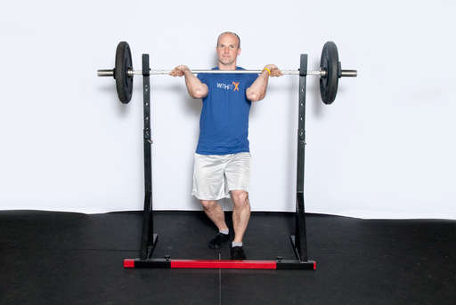 Rest a barbell on the front of your shoulders, with your elbows bent and up to keep the bar in place. Your hands should hold the bar in place, but the weight should be on your shoulders.