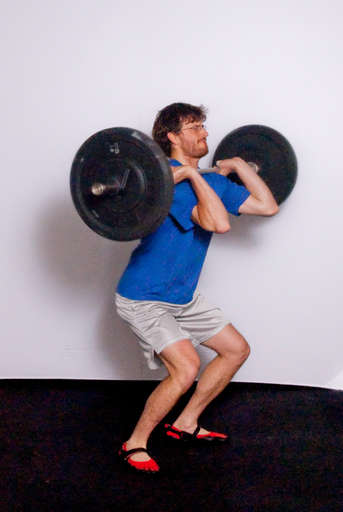 Catch the bar on your shoulders. Your feet should move out slightly so you land with your feet shoulder width apart.