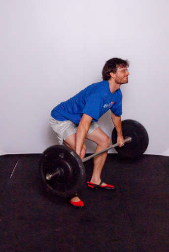 Lift the barbell off the ground by extending your knees and hips. Keep your arms straight.