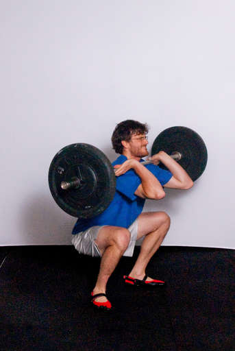 Catch the bar on your shoulders while at the same time moving into a [Front Squat]. Your thighs should be at least parallel with the floor. Your feet should move out slightly so you land with your feet shoulder width apart.