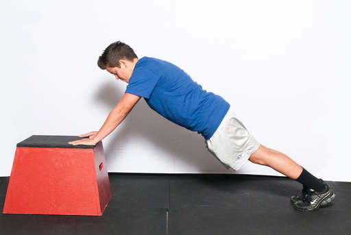 Position yourself in a push up position. Place your hands on a raised object, such as a box or bench. Your body should be in a straight line.