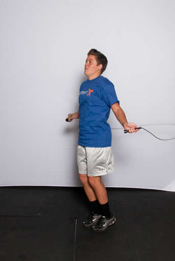 Stand with your feet approximately hip width apart and your arms down at your side, holding the jump rope behind you.