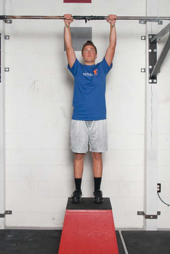 Stand below the pull up bar. Grasp the pull up bar with an overhead grip, with your hands over the bar and approximately shoulder width apart. The bar should be low enough that your feet remain on the floor. If it isn't, stand on a box.