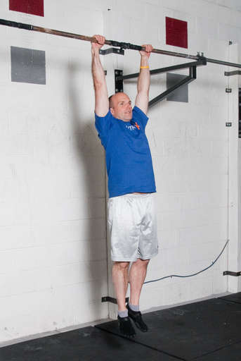Grasp a pull up bar with an overhand grip with your arms slightly wider than shoulder width apart. Hang straight down from the bar.