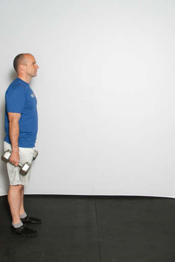 Stand with your feet approximately hip width apart, dumbbells down at the side of your body.