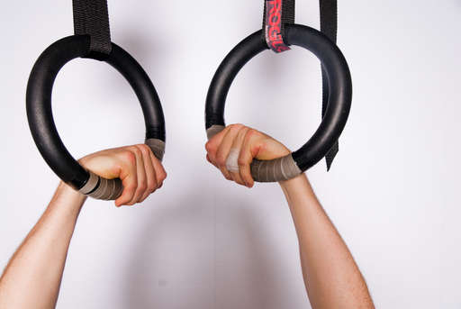 Place your hands on the rings in a false grip. A false grip is achieved as placing your wrists on the rings with your fingers pointing inward, then turning the fingers towards your body and grasping the rings while keeping your wrists on the rings. This grip will feel awkward and uncomfortable at first, but it is important to doing proper muscle ups.