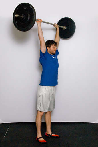 Finish by fully extending your legs while holding the bar overhead.