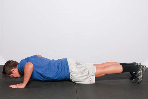 Lower your body until your chest, chin and quads touch the ground at the same time.