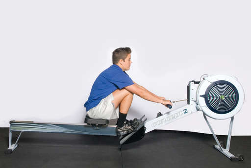 Sit straight on the rowing machine seat and place feet inside foot plate stirrups.  Grasp the bar with an overhand grip.