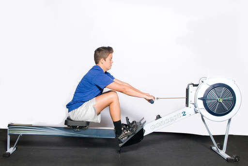 Bend your knees and extend your arms out towards the wheel of the machine. Your back should be only slightly arched.