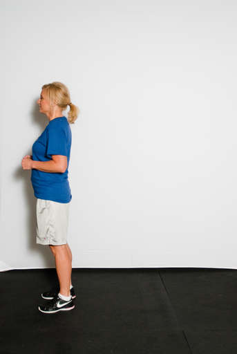 Stand erect with shoulders back, head erect and facing backward direction.