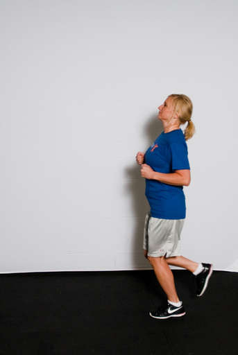 Alternate your steps backwards as your arms pump in the same fashion as if running forward.  While the direction you watch is backward, the head is held straight as it would be if running forward.