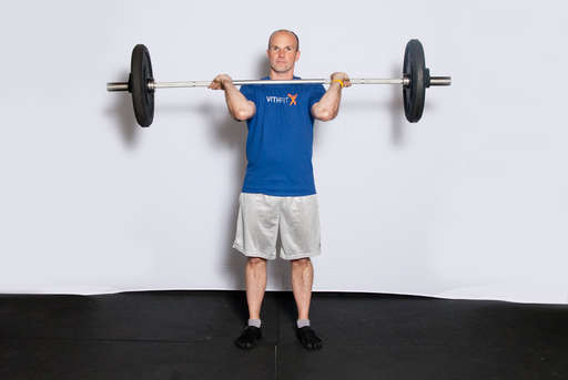 Stand, grasping a barbell in an overhand grip, resting on your shoulders.