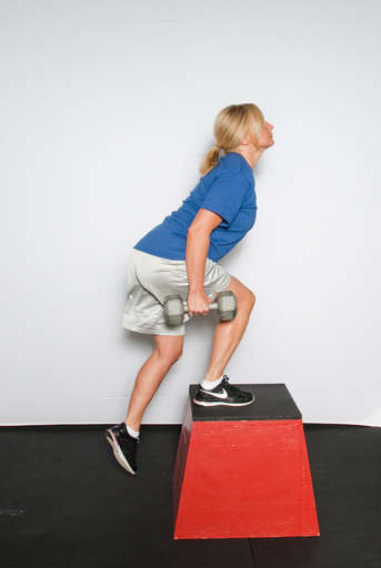Extend your knee and hip to stand up on top of the box.