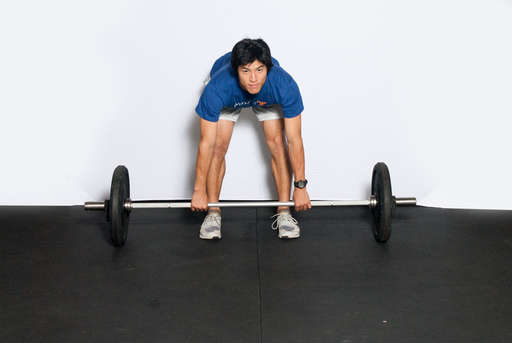 Bend at the waist, keeping your legs straight. Grip the barbell using an overhand or alternating grip.