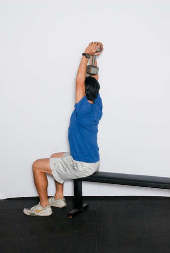 Sit straight up. Grasp a dumbbell in an overhand grip and raise your arms straight up so that the weight is right above your head. Your elbows should be facing forward.