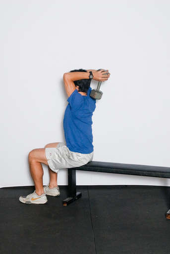Bend your arm at the elbow, lowering the weight behind your head.