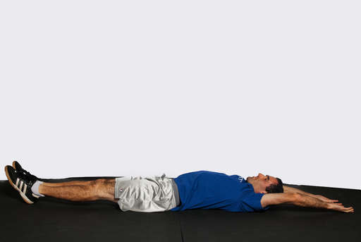 Lie flat on your back on the floor with your legs completely straight, arms stretched over your head.