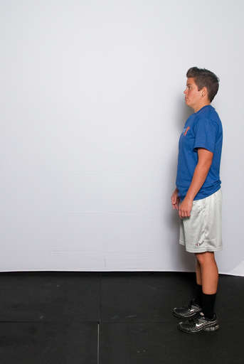 Stand with your feet approximately shoulder width apart and your arms down at your sides or back behind your head.
