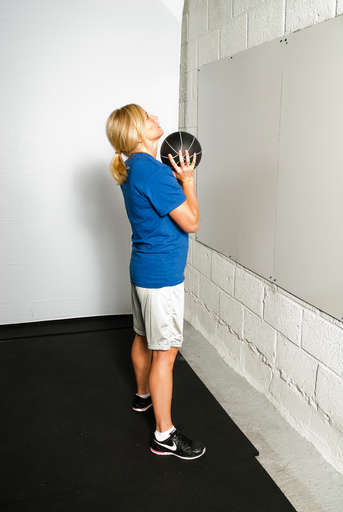 Stand about 1-2 feet away from the wall with your feet shoulder width apart. Hold the medicine ball in front of your face with your arms bent.