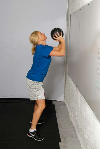 Explosively extend your arms and legs, bringing your body to a standing position and throwing the ball at your target.