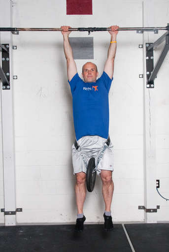 Stand below the pull up bar. Grasp the pull up bar with an overhead grip, with your hands over the bar and approximately shoulder width apart. Attach additional weight via a weight belt, chain, or other method. Hang from the pull up bar, so that your arms and legs are completely straight.