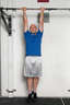Grasp the pull up bar with your palms facing you, approximately shoulder width apart. Hang from the bar, so that your arms and legs are completely straight.