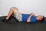 Lie on your back on the floor with your legs bent at a 90 degree angle. Place your hands in front of your chest.